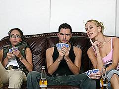 Three young people are playing strip poker and the guy keeps losing so he had to get naked.  He starts to get hard and the blond girl starts giving him a hand job.  The brunette girl in the corner of the couch looks a little horrified by her friend giving him a hand job.  They go back and forth with bantering and joking.  The blond girl is trying to turn him on more and make his cum quicker.  He puts his head back in pleasure.  The brunette girl is laughing in the corner.  He ended up cumming so she pointed his dick toward his chest so he came on himself.  She sticks a playing card with cum on it to his forehead.