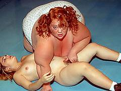 This is definitely going to be one of the strangest porn videos you have seen in a while!  The action happens inside a wrestling ring, with enormous fatties Sindee Williams and Zazie fighting each other in pro wrestling style.  The humongous pumpers hurl each other around the ring, body slamming each other and rolling around on the floor.  The referee is tiny but chubby midget Chuy Bravo, who facilitates the action like a pro.  Somehow the two fatties end up naked, with the plump midget pounding them both in their sloppy, fat holes.  However, the fella doesn\'t satisfy the plumpers, so they decide to beat him up!  Definitely a very weird one!