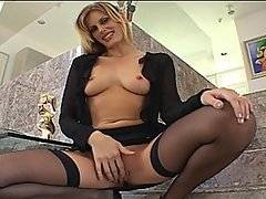 Tall blonde MILF Darryl Hanah strips out of her black outfit to show off her natural tits, bald pussy and round ass. She soon joins a much younger man, and she gets on her knees to show her experience. She sucks his hard cock, blowing him and licking his balls while looking up at him. She lays back so he can eat her out, fingering her snatch and licking her clit before he fucks her missionary. She climbs on top to ride him reverse cowgirl, And he lays beside her to give it to her while spooning her. He bends her over to fuck her up the ass doggy style, and, after reaming her anally, he finally blows his load all over her for a messy facial.
