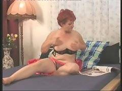 Redhead old tart watches journal and tenders her eager pussy on bed.