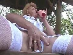 Grandma in white lingerie tenders her pussy outdoor.