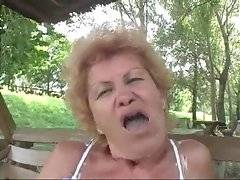 Horny old chick plays big dildo on the bench in park.