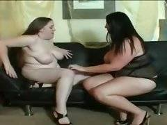 Lovely babes are satisfying each other on the sofa