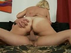 Horny busty milf sucks some dick before sitting down on it.