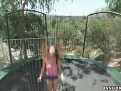 Naughty brunette readily starts to jump on trampoline to entertain her friend.