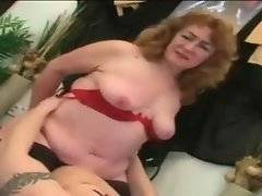 Horny granny is undressing and caressing herself on stairs.