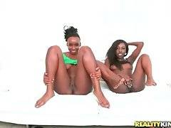 Two black babes lie on bed and rub their pussies together.